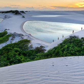 A group of tourists crossing the sand dunes and lagoons during dusk.