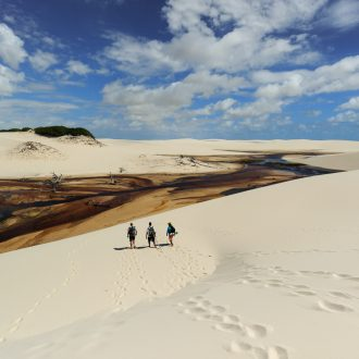 A group of tourists crossing sand dunes and lagoons.